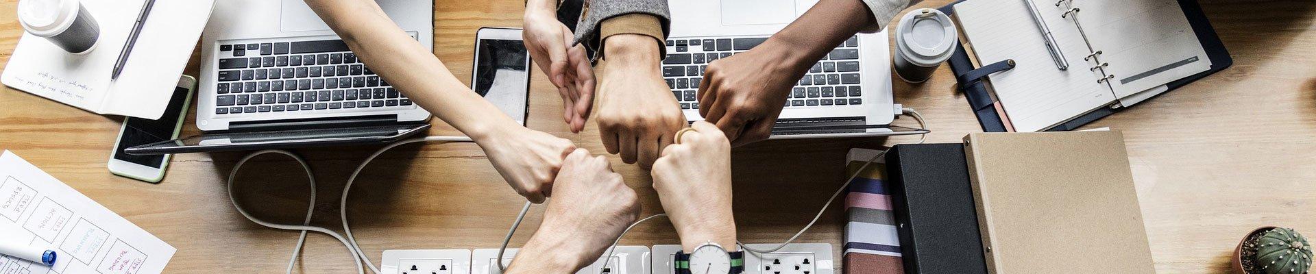 Teammitglieder legen die Hände zusammen